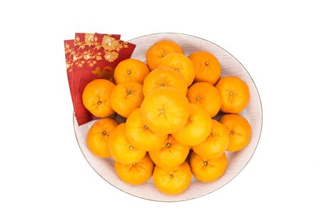 mandarin oranges: Heap of mandarin oranges in tray with decorative red packets with good luck greeting character in Chinese on white background Stock Photo