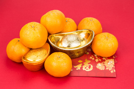 mandarin oranges: Mandarin oranges with decorative gold nugget, and red packets with Good Luck character in Chinese on red background