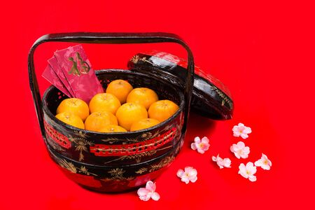 basket: Juicy mandarin oranges in traditional basket with Good Luck Chinese character on red packets in red background