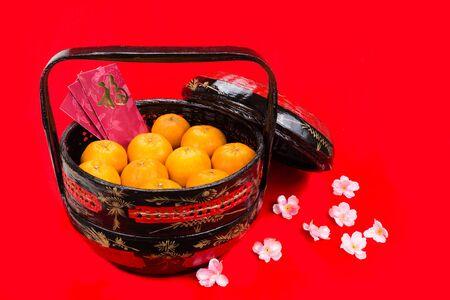 naranja: mandarinas jugosas en cesta tradicional con buena suerte caracteres chinos en paquetes de color rojo en fondo rojo