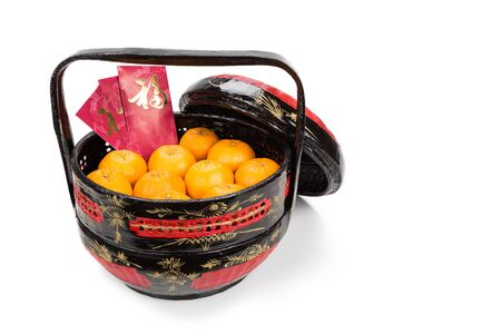 chinese new year food: Juicy mandarin oranges in traditional basket with Good Luck Chinese character on red packets in white background