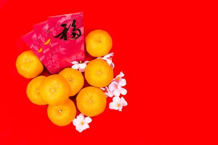mandarin oranges: Mandarin oranges with red packets bearing Good Luck character in Chinese on red background