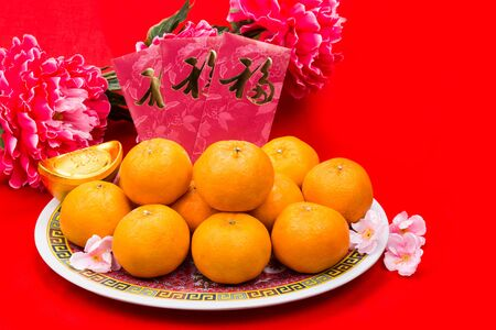 mandarin oranges: Mandarin oranges on plate with Good Luck festive greetings Chinese character on red packets against red background
