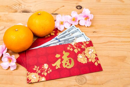 red packet: Hung Bao or red packet with Good Fortune Chinese character filled with US Dollar notes, displayed with mandarin oranges Stock Photo
