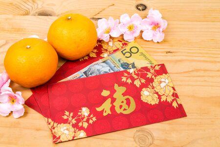 dollaro: Hung Bao o pacchetto rosso con carattere Good Fortune cinese pieno di valuta Dollaro Australiano, visualizzata con mandarini Archivio Fotografico