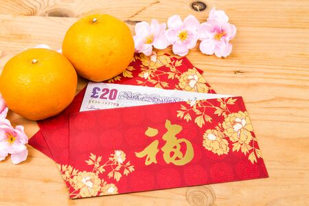 mandarin oranges: Hung Bao or red packet with Good Fortune Chinese character filled with Sterling Pound currency, displayed with mandarin oranges Stock Photo
