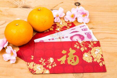 flores chinas: Hung Bao o paquete rojo con el carácter de la buena fortuna china llena con China Yuan Renminbi, que se muestra con mandarinas