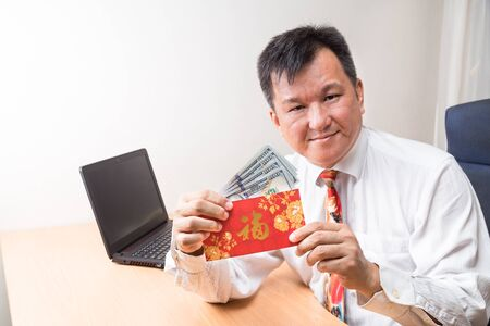 packet: Employee displaying red packet with Good Fortune Chinese character, and money received from employer in office Stock Photo
