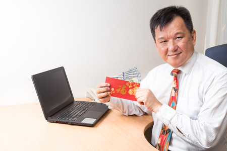 good fortune: Employee displaying red packet with Good Fortune Chinese character, and money received from employer in office Stock Photo