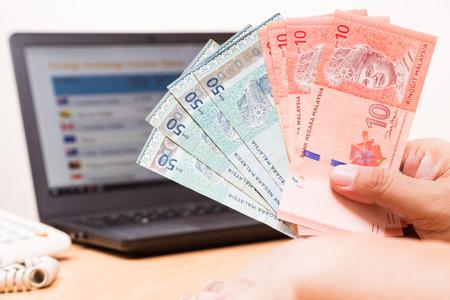 Hand houden van Maleisië Ringgit in bureau met computer scherm met valutamarkt tafel in de achtergrond
