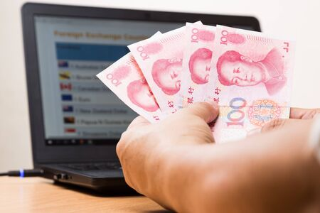 yuan: Hand holding China Yuan  in office with computer screen showing foreign exchange table in background Stock Photo