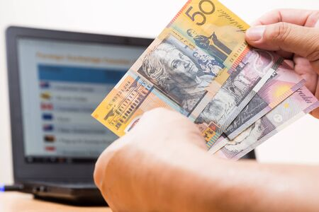 hand with money: Hand holding Australian dollar in office with computer screen showing foreign exchange table in background Stock Photo