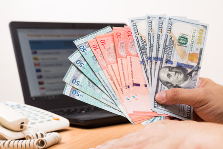 Hand sorting Malaysia Ringgit and US Dollar in front of currency exchange chart on computer screen.