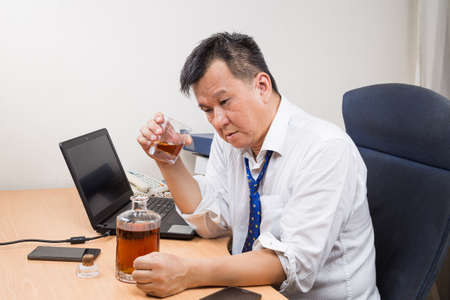 hard liquor: Frustrated and stressful Asian business manager drinking hard liquor in office