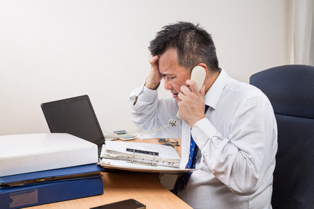 stress management: Busy, stressful and frustrated Asian business manager talking on telephone in office
