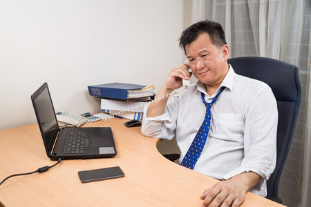 landline phone: Busy, stressful and frustrated Asian business manager talking on telephone in office