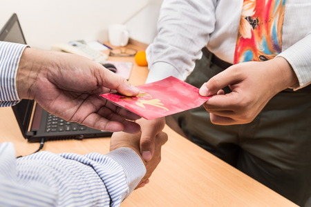 returning: Employee receiving red packet with Good Fortune Chinese wordings, from employer upon returning to work in office