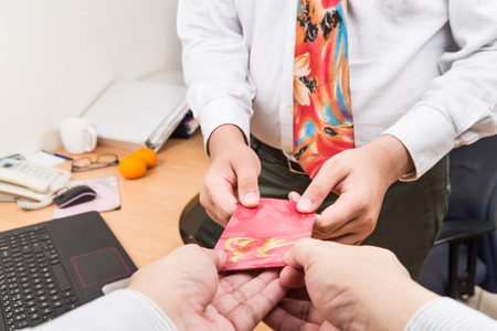 packet: Perspective view of employer giving red packet with Good Fortune Chinese wordings to employee upon returning to work in office Stock Photo