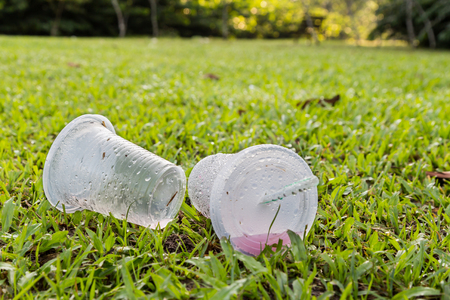 dirty environment: Environmental unfriendly non-biodegradable PVC cups with straw litter in public park