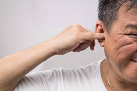 dedo me�ique: El hombre no-higi�nica limpieza del o�do con el dedo con la expresi�n cosquillas Foto de archivo