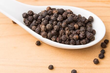 piperine: Spoonful of aromatic and spicy black pepper corns on wooden surface