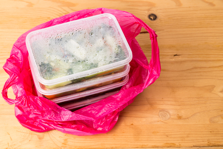 the convenient: Convenient but unhealthy disposable plastic lunch boxes with take away meal in plastic bag on wooden table Stock Photo