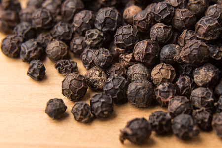 piperine: Heaps of aromatic black pepper corns on wooden surface