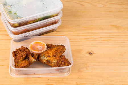 Convenient but unhealthy disposable plastic lunch boxes with take away meal on wooden table