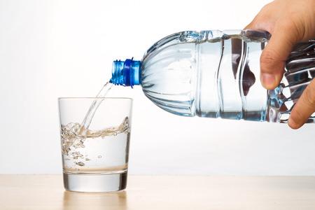 Hand gieten verfrissend natuurlijk mineraalwater van fles in transparant glas op een witte achtergrond Stockfoto