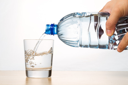 Hand pouring refreshing natural mineral water from bottle into transparent glass in white background Archivio Fotografico