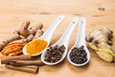 piperine: Ingredients for healthy turmeric tea consisting ginger, cinnamon, cloves and black pepper Stock Photo