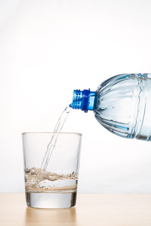 orientated: Hand pouring refreshing natural mineral water from bottle into transparent glass in vertical orientated shot Stock Photo