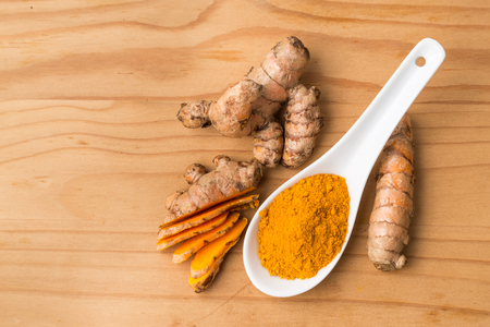 piperine: Fresh and grounded aromatic turmeric roots on wooden surface Stock Photo