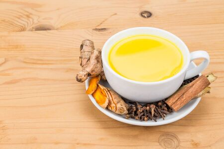 piperine: Aromatic milk tea with ginger roots, cinnamon, cloves and black pepper offers many wellness health benefits Stock Photo