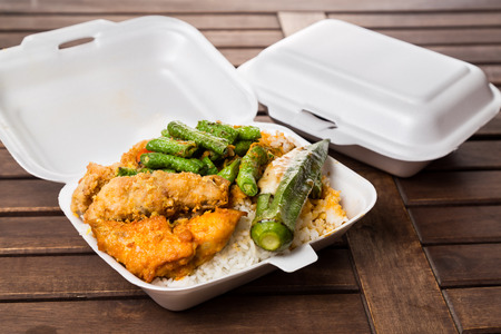 Convenient but unhealthy polystyrene lunch boxes with take away meal on wooden table