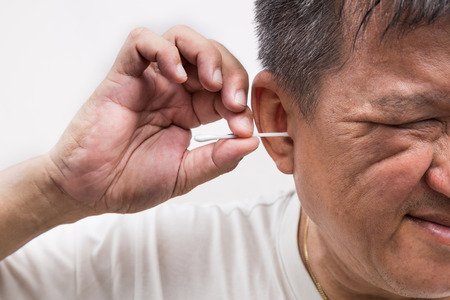Man cleaning ear with cotton buds stick with a ticklish expression.