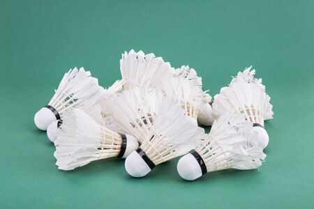 heaps: Heaps of used and worned out badminton shuttlecock on green mat PVC court Stock Photo