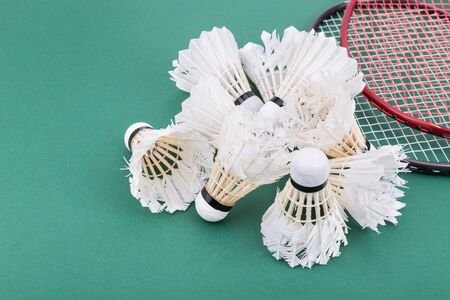 badminton racket: Group of used and worned out badminton shuttlecock and rackets on green mat PVC court