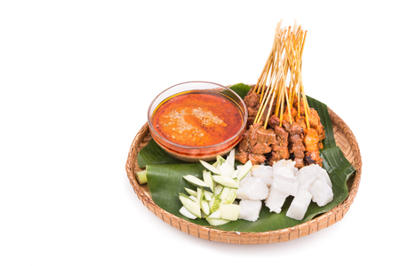 Freshly barbecue chicken and beef satay with gravy, rice, cucumber and onion served on traditional rattan weaved plate with banana leaf Stock Photo