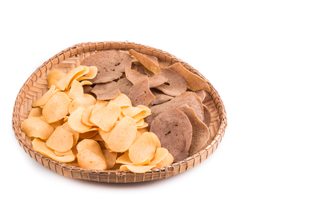 keropok: Dried raw prawn and fish crackers on traditional rattan tray in white background