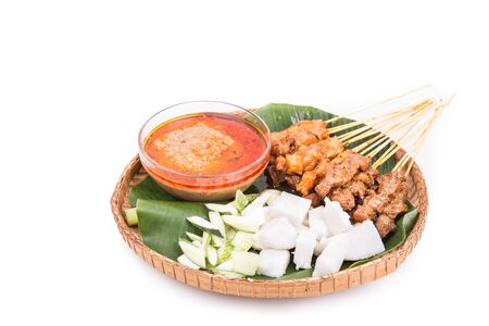 carne de pollo: Freshly barbecue chicken and beef satay with gravy, rice, cucumber and onion served on traditional rattan weaved plate with banana leaf Foto de archivo