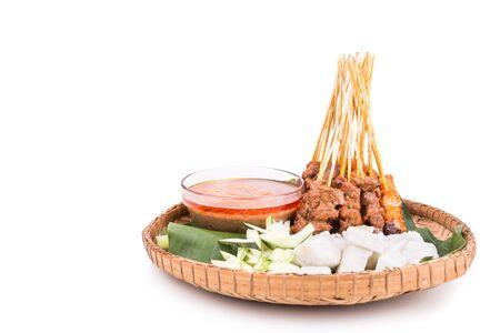 新鲜的烤鸡和牛肉沙嗲配肉汁,米饭,黄瓜和洋葱,传统的藤条和香蕉叶盘子