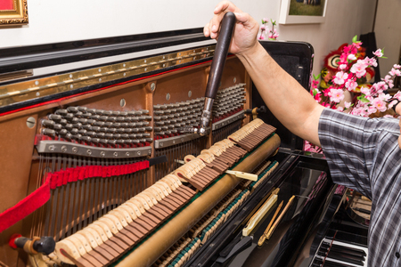 Closeup on hand tuning an upright piano using lever and tools