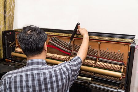 Technician cum musician tuning an upright piano using lever and tools