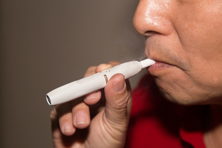 refills: Smoker smoking hybrid smokeless cigarette device that uses real tobacco refills, a hybrid technology between analog and electronic cigarettes. Stock Photo