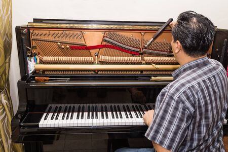upright piano: Technician cum musician tuning an upright piano using lever and tools Stock Photo