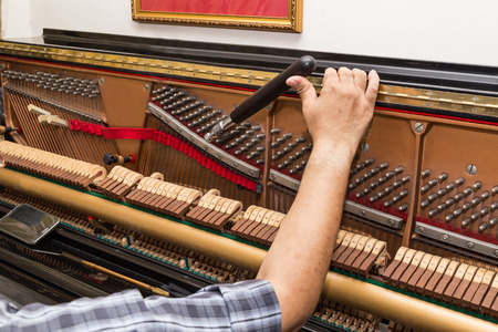 upright piano: Closeup on hand tuning an upright piano using lever and tools