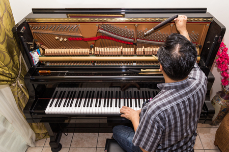 Technician cum musician tuning an upright piano using lever and tools Stockfoto