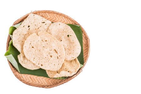 keropok: Freshy fried delicious fish crackers snack served on traditional rattan tray with white background Stock Photo