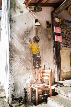 ernest: PENANG, DECEMBER 16, 2015:  Mural artwork by artist Ernest Zacharevic entitled Boy On Chair. The mural is located at Leboh Cannon.